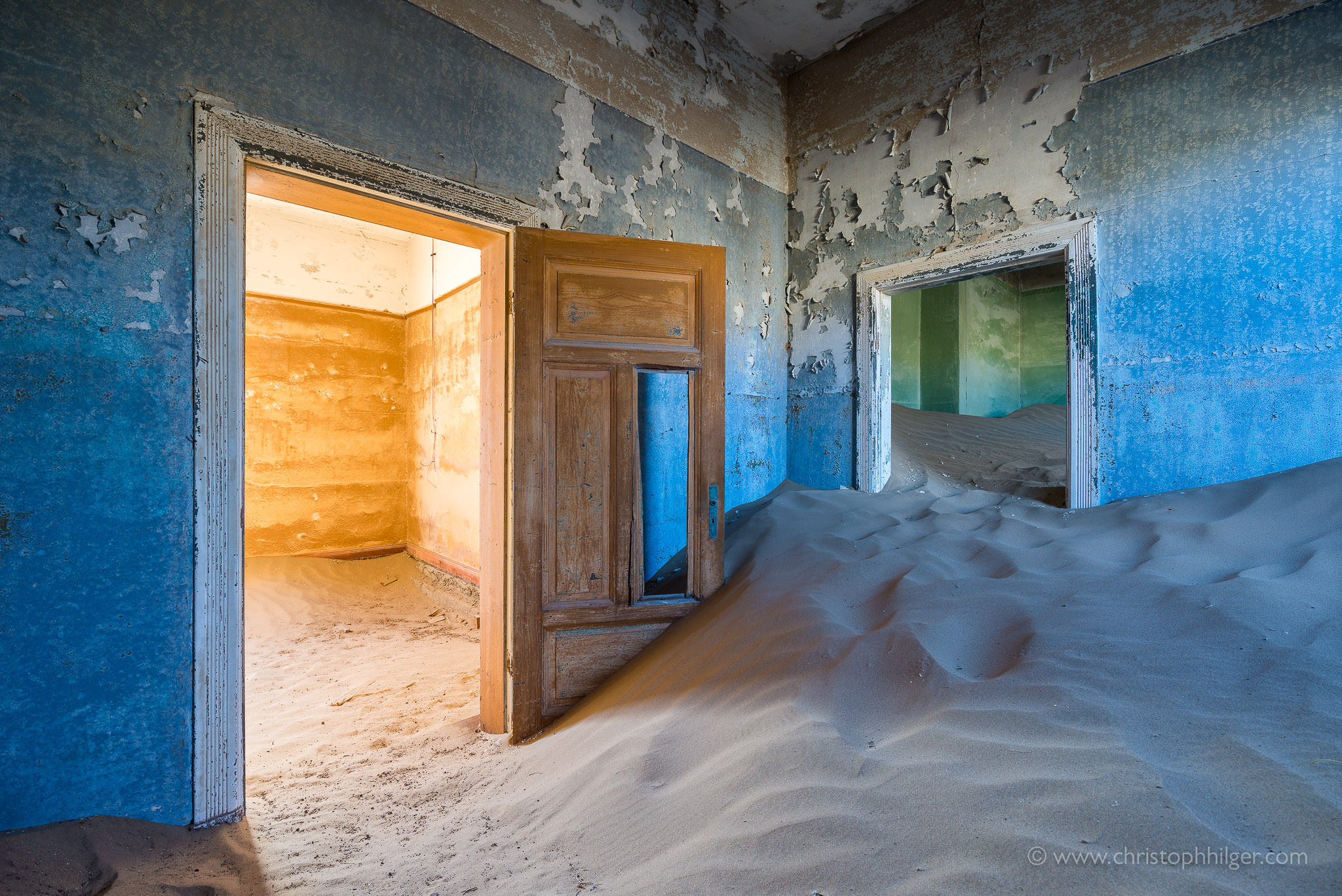 Bunte Räume und Sand in verlassenem Haus in Kolmanskop, Namibia