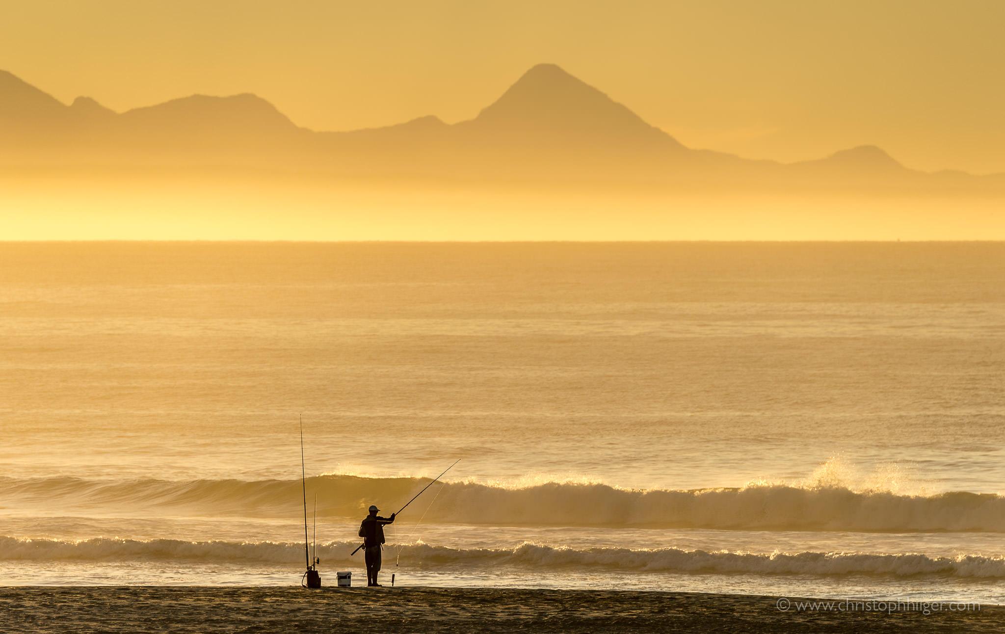 Angler bei Sonnenaufgang in Plettenberg Bay, Südafrika